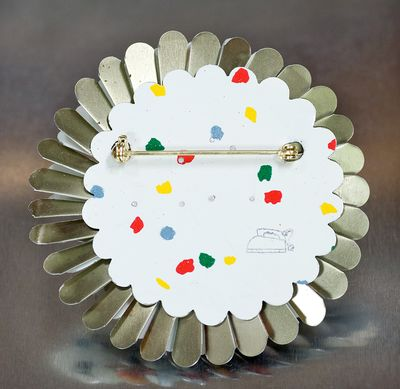APRIL FLOWER BROOCH by harriete Estel Berman is made from recycled tin cans.