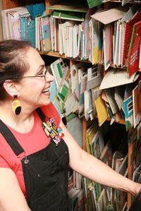Harriete Estel Berman working in the studio in front of her wall of tins.