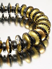 Black and gold Identity Necklace by Harriete Estel Berman constructed from recycled tin cans.
