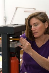 Alison Antelman working at her hydraulic press in the studio.