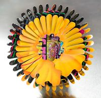 Harriete Estel Berman Flower pin in brillian yellow orange with black says Grand Slam in the center.