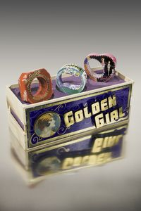Golden Girl Fruit Crate functions as a jewelry display by Harriete Estel Berman constructed from recycled tin cans.