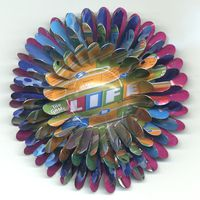 Life Flower Brooch by Harriete EStel Berman is constructed from post consumer recycled tin cans.
