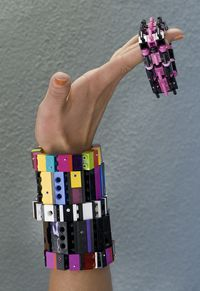 Model  holding  bracelets made from Legos