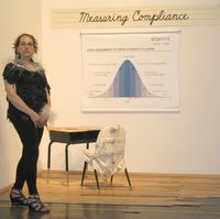Harriete Estel Berman standing near Measuring Compliance at the exhibition Manufracturedbstanding