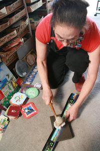 Harriete flattening tin cans working in the studioTINS.100