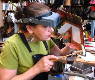 Harriete Estel Berman working in the studio on a Tu Bishvat Seder Plate in her studio