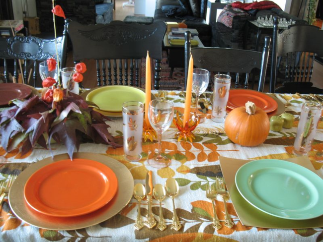 Vintage fabric, dishes, glasses, and flatware with atomic candlesticks.