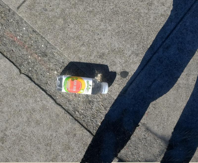 Green-plastic-bottle-sidewalk-trash-close-large