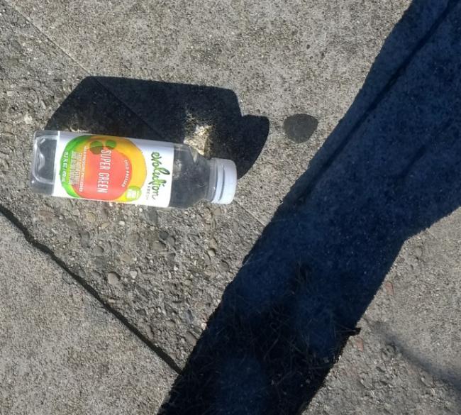 Green-plastic-bottle-sidewalk-trash-closer-large