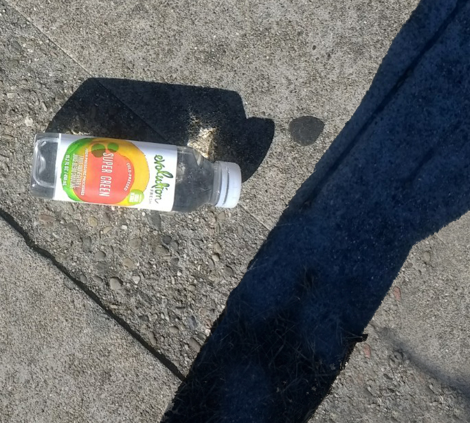 Green-plastic-bottle-sidewalk-trash-closer-large